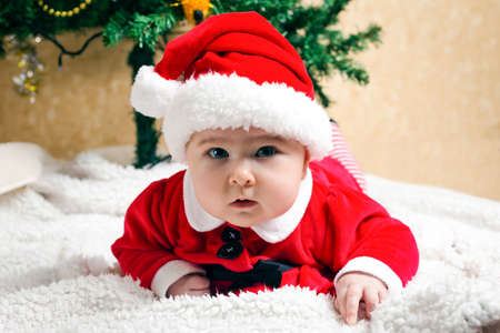 Cute little christmas child wearing santa claus suit and and looking at the viewer, christmas tree at the background