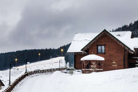yule log: Wooden house in the mountains in winter, a ski track in the background. shallow DOF