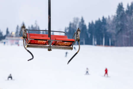 lonley, red sky chair in the mountain, skiers at the background