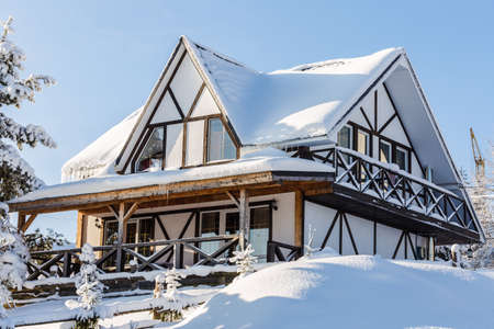 close-up photo of Snow-covered wooden building in the mountains, Construction crane  in the background Фото со стока