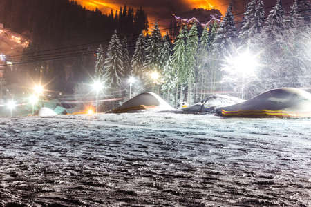 scenic spots: night mountain landscape, snow-covered skiing, empty track route, illuminated by artificial light, view from the top of the mountain. Bukovel, Ukraine