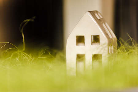 A minimalistic model of a white house carved and sliced from plastic, on a green grass