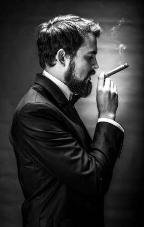 black and white portrait of bearded smoking cigar gentleman in a suit