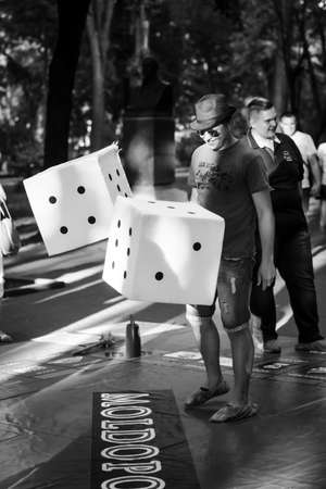 6 june 2015 an unidentified guy plays in a monopoly on the street with big cubes,black and white photo, Chisinau, Moldova
