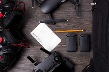 drone dji mavic air and rollers, near a backpack and akamulyatorov, with a leaf for planning, on a woody background