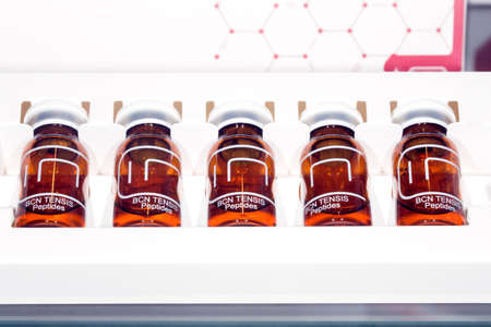 BCN TENSIS Peptides ampoules on white background, close-up, cosmetic tools