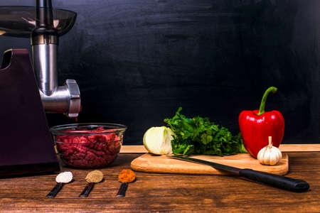 Küchenstillleben vom elektrischen Fleischwolf, von den Gewürzen in den Löffeln, in der Petersilie, in der Zwiebel, im Knoblauch und im Paprika mit einem Messer auf einem Holztisch auf dem Hintergrund eines Brettes für Kreide mit Raum für Text