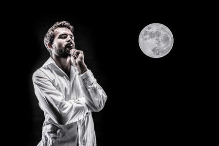 man pensively generates an idea on the background of a full moon Banco de Imagens