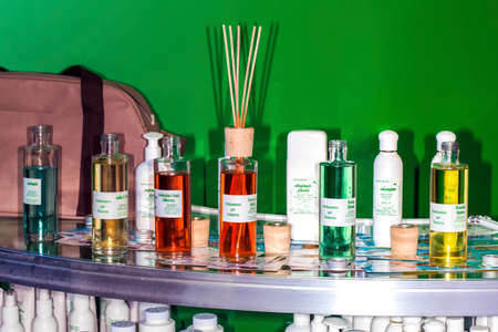 transparent bottles with body care products and hair for adults and children are on the table, on a green background