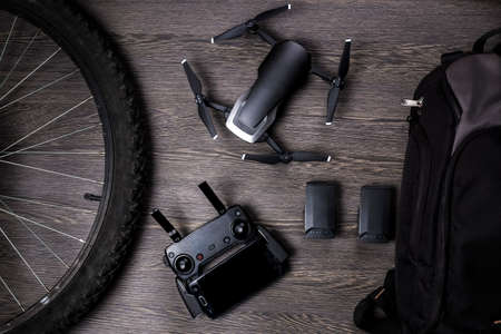 drone and bicycle wheel, near a backpack and battery, with a leaf for planning, on a woody background, concept of portable quadrocopter