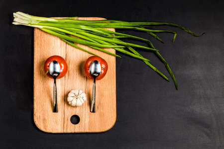 Cartoon funny face surprised tomatoes, spoons, garlic and green onion lined up in the kitchen wooden planks Stock Photo