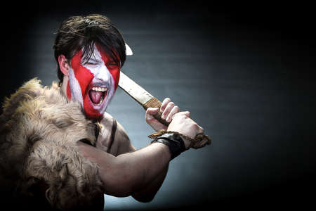 Portrait of man in war paint, with an ax in his hands, a warrior brandishing an ax furiously screaming, barbarian of ancient times, Viking and savage. Stock Photo