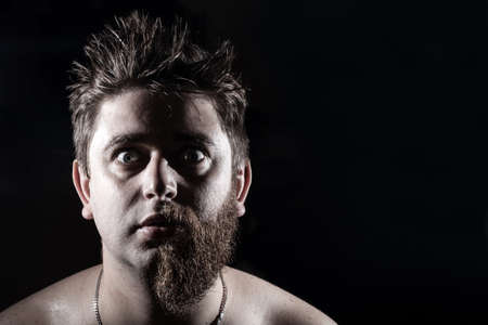 man in half shaved with wide open eyes looking at the camera on a black background Reklamní fotografie
