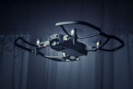 drone dji mavic air, quadroopter flies in the room, with protective accessories on it, toned image