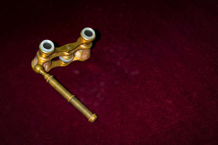 Opera glasses on burgundy background with space for text