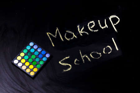 Eye shadow near the inscription makeup school on a black background