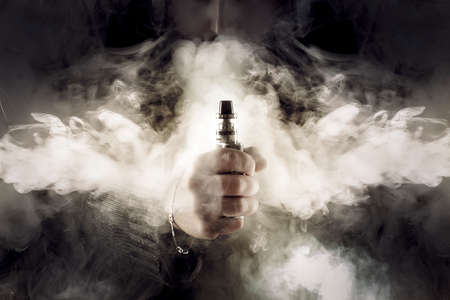 electronic cigarette in hand in the middle of thick smoke, background image