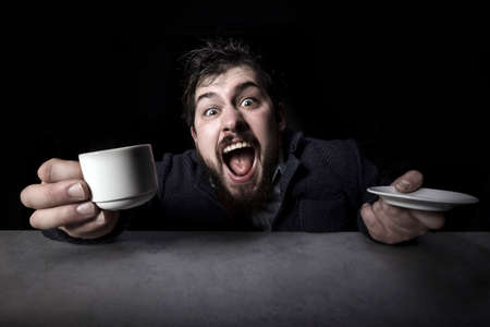 cheerfully crazy bearded man emotionally shouts into the camera with a cup of coffee in his hand