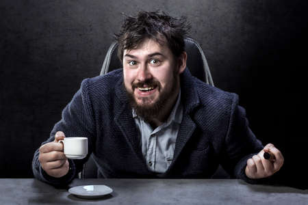 portrait of a crazy bearded man in the director's chair with a cigar and coffee in hand Imagens - 110699551