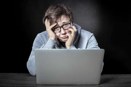Frustrated programmer with glasses is sitting at a laptop and looking at the camera with disappointment, concept of failure