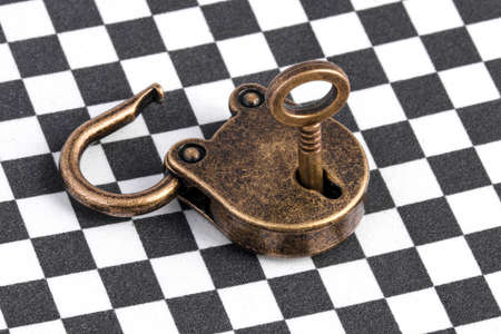 old open lock bronze with a key on a chess surface Banco de Imagens