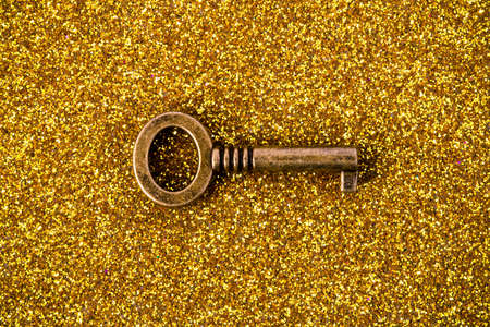 image of bronze key on a golden background