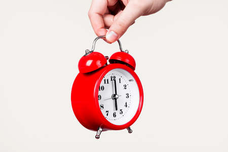 red clock with alarm in hand on a light background, wake up concept in the morning
