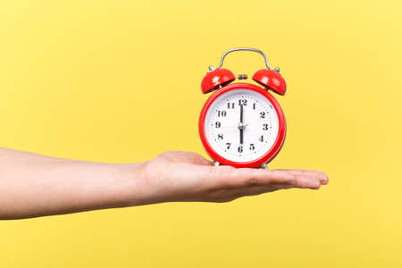 red clock with alarm on hand on a yellow background, wake up concept in the morning Stock Photo