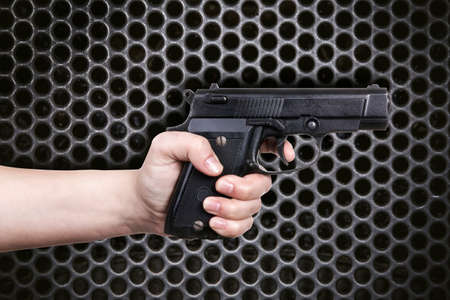 female hand holding gun on dark gray circle mesh pattern