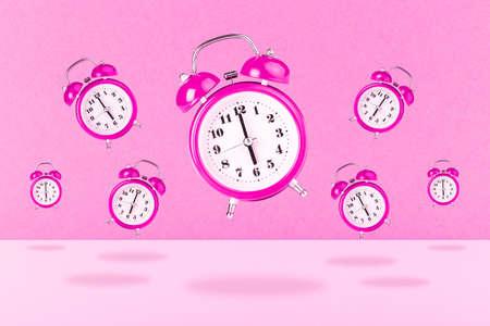 background of pink alarm clocks, concept of awakening