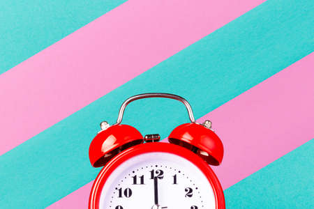 Half part of red alarm clock on colorful blue-pink background with copy space.