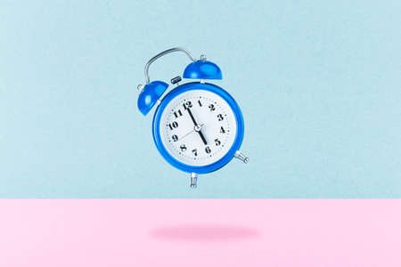 blue alarm clock on a pink azure background