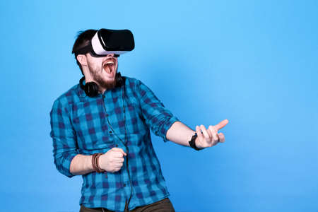 bearded man in glasses of virtual reality, emotionally playing shooters in VR on blue  background Standard-Bild - 117924144