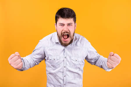 aggressive man screaming clenched fists on orange background