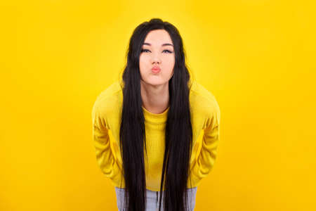 girl in a yellow sweater, grimaces inflates cheeks and lips Banco de Imagens