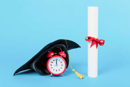 graduation cap on red clock near diploma, image on a blue background, concept graduation time Banque d'images