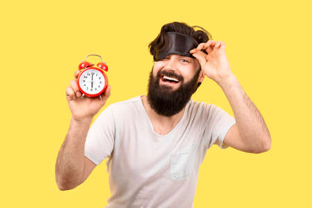 Happy bearded man with sleep mask and alarm clock on yellow background, concept good morning
