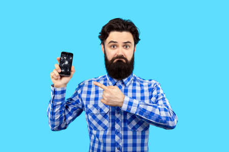 bearded sad hipster man pointing finger at broken smartphone screen, image on blue bacground, search concept gsm service