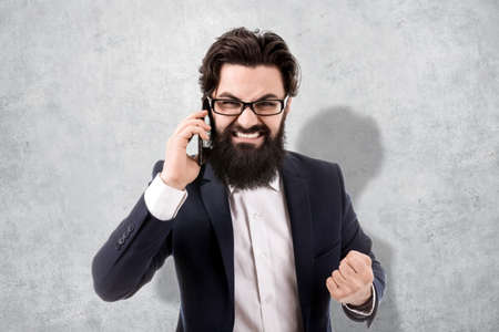 aggressive bearded businessman swears on the smartphone, image on the background a concrete wall