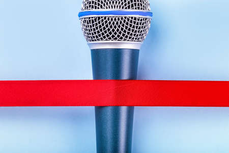 Microphone with red tape over blue background, music concept