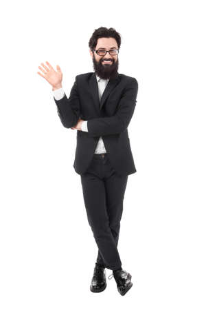 Hi, nice to see you. Friendly-looking attractive bearded businessman waives hand in hello gesture while smiling cheerfully, saluting concept