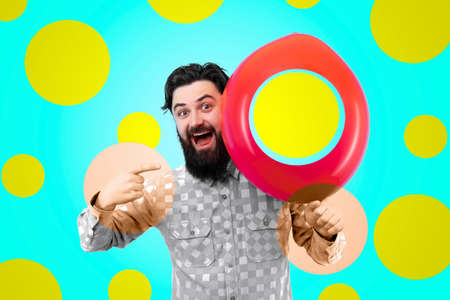 bearded smiling man pointing away on a colored balloon over azure background