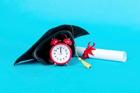 graduation cap on red clock near diploma, image on a blue background, concept graduation time 写真素材