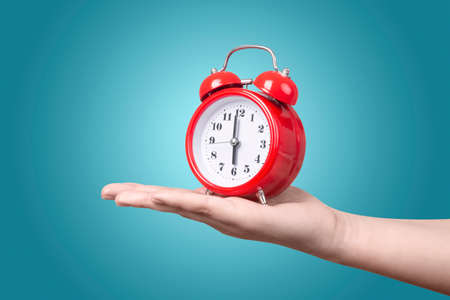red clock with alarm on hand over blue background, wake up concept in the morning Stock Photo