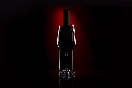 Glass and bottle of red wine on a dark red background Banque d'images - 124901039