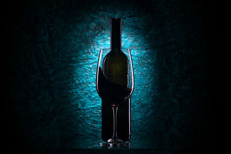 Glass of red wine and wine bottle on azure stone background, drink against the wall in the old cellar
