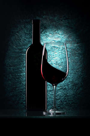 glass of red wine and bottle  on azure stone background, drink against the wall in the old cellar