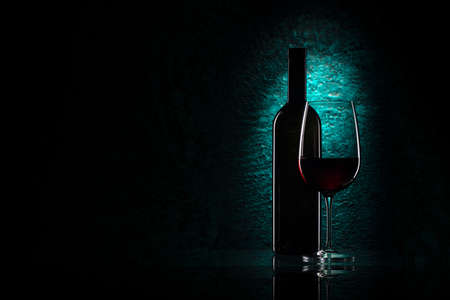 Red wine glass and bottle on azure stone background, drink against the wall in the old cellar