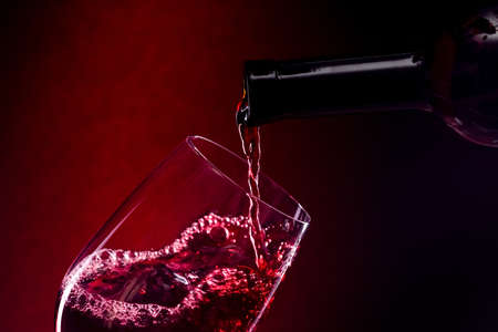 Verter el vino tinto en el vaso sobre fondo rojo.