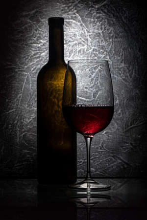 Red wine glass and wine bottle on gray stone background, drink against the wall in the old cellar